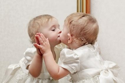 Bébé qui embrasse sa réflexion dans un miroir